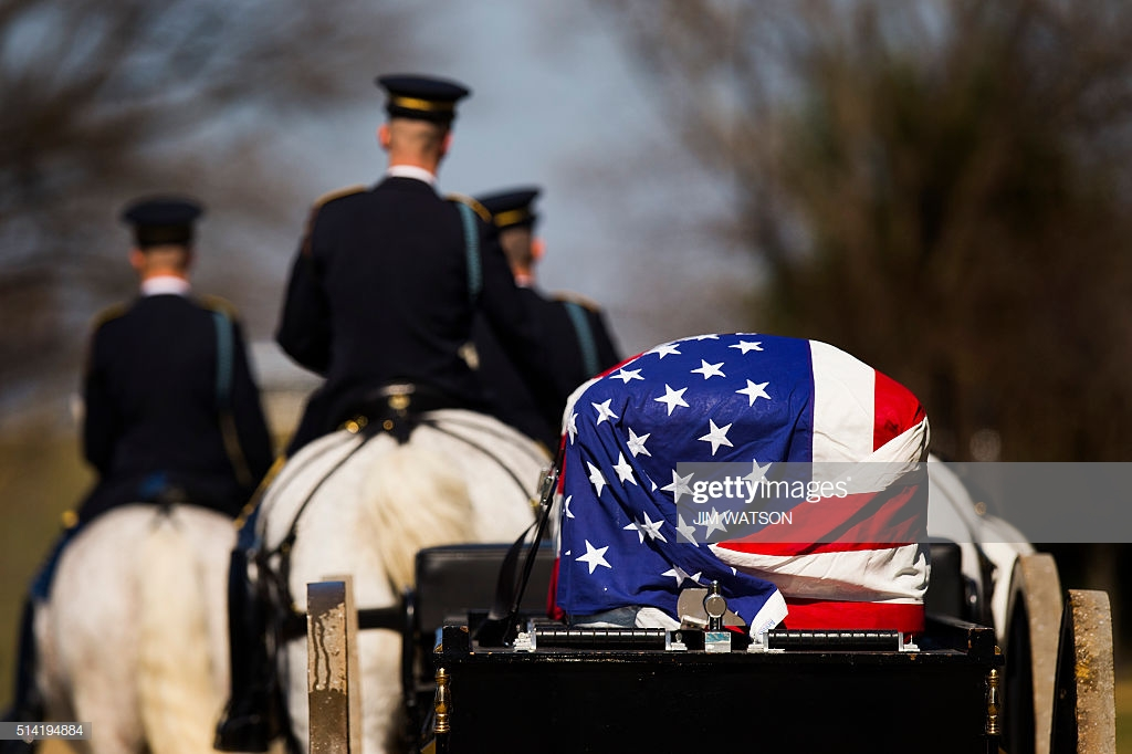 An American flag draped coffin is taken to a burial at Arlington.jpg